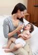 Mum giving medicine to baby using syringe