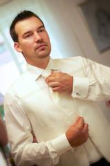 Bräutigam kleidet sich vor Spiegel