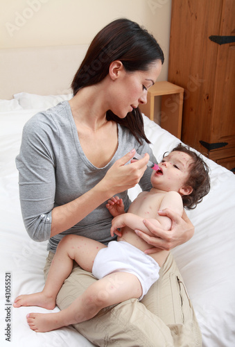 Mum giving medicine to baby using syringe