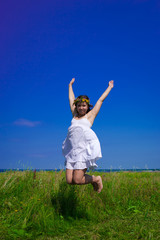 happy woman jumping at the field at sunny day