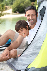 Father and son campink by a lake