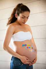 Beautiful pregnant model expecting newborn wearing jeans and whi