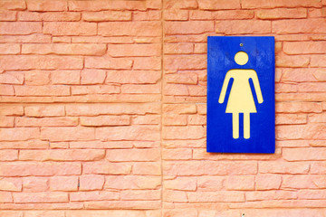 Sign of toilets and brick wall