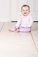 Baby Girl Sitting on Tiled Floor