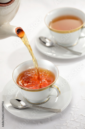 Pouring tea from the tea pot to the cups