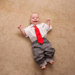Smiling newborn baby in business suit and red tie