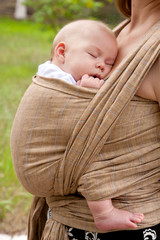 Newborn baby sleeping in a sling, in the embrace of her mother