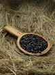 Black beans in a wooden bowl on the hay