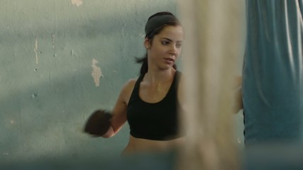 Young hispanic woman training and boxing in gym