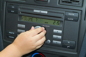 Child adjusts the volume of car radio