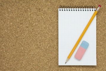 Pencil with eraser and notebook on cork