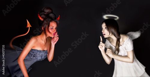 Leinwanddruck Bild Portrait of angel and devil girls and copyspace between them.