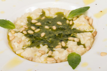 photo of delicious risotto dish with herbs and cedar nut on whit
