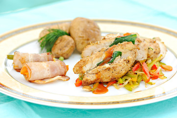 meal with prepared chicken meat, bacon rolls and vegetables