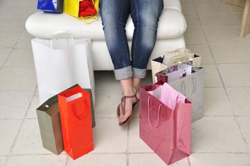 Frauenbeine hängen vom Sofa mit Einkaufstüten