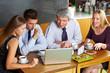 Geschäftsleute schauen auf Laptop in Café