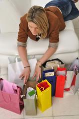 Frau liegt auf Sofa mit Einkaufstüten