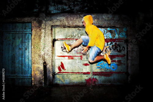 Young man jumping on grunge graffiti wall