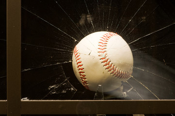 Baseball smashing glass window.