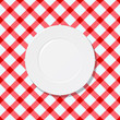 White plate on red and white checked tablecloth