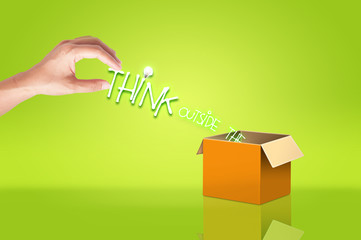 Hand holding think out side the box text for concept idea