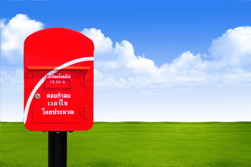 Red thailand post box on green grass and blue sky background