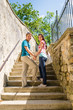 Young couple smiling holding hands on stairs