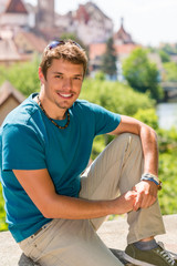 Young man visit city sightseeing smiling posing