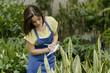 Young female gardener working at a nursery garden