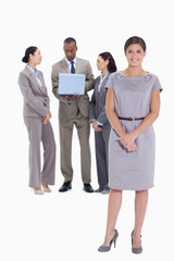 Woman holding her hands with co-workers talking in the backgroun