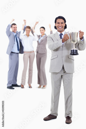 Businessman smiling and holding a cup with people cheering behin