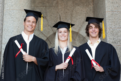 Graduates holding their diploma while posing