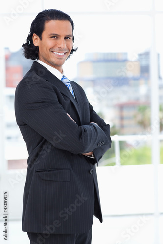 Smiling executive crossing his arms while looking at the camera