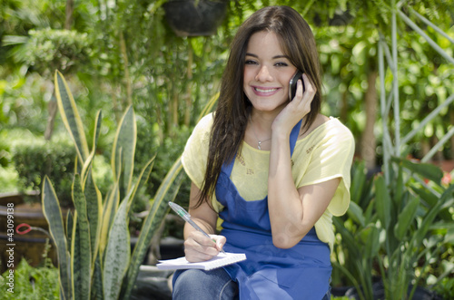 Happy female gardener taking an order from a customer