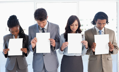 Young business team showing blank sheets while bowing their head