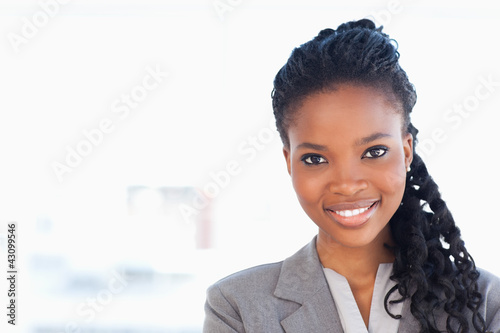 Young employee standing upright in front of a bright window whil