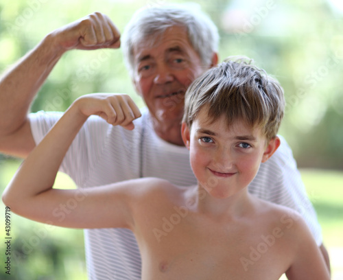 Grandfather and grandson flexing biceps