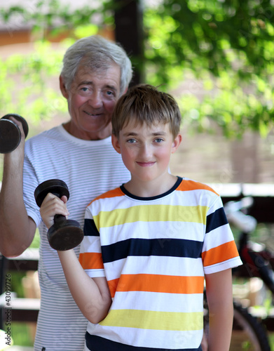 Grandfather and grandson of exercising with dumbbells