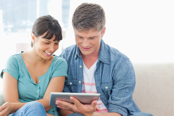 A smiling couple sit on the couch and use a tablet