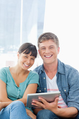 A smiling couple looking into the camera while holding a tablet