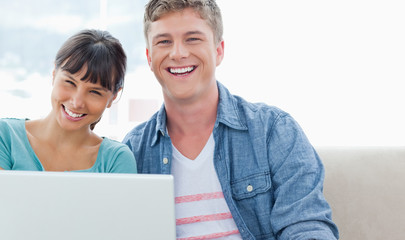 A laughing couple sitting on the couch with a laptop as they loo