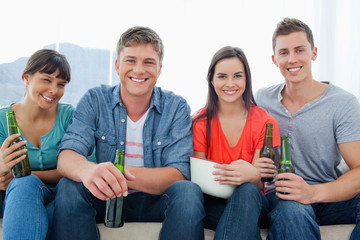 A smiling group sitting on the couch while holding beers