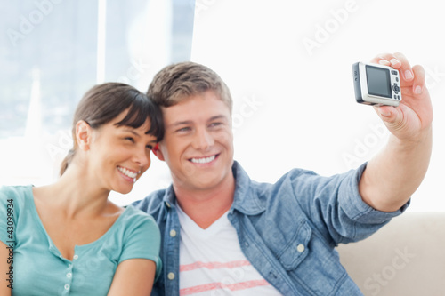 A smiling couple pose for a romantic photo together