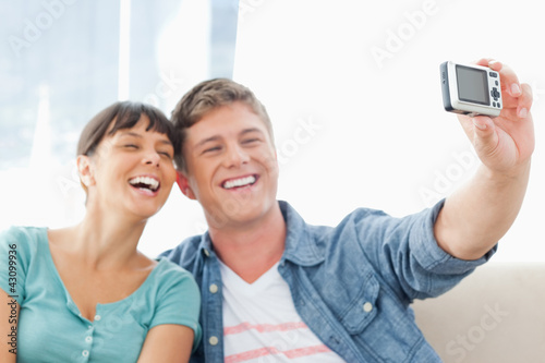 A couple laughing together as they pose for a photo