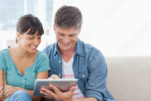 A couple sitting and using a tablet pc together