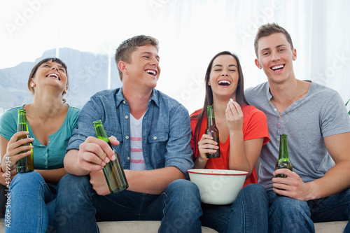 Laughing group of friends sitting with beers in their hands and