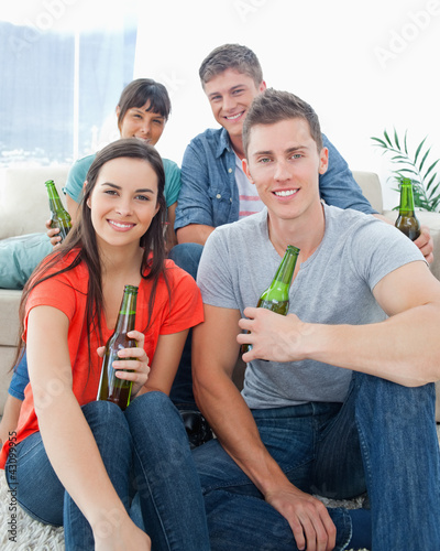 Two people sitting on the couch with the other two sitting on th