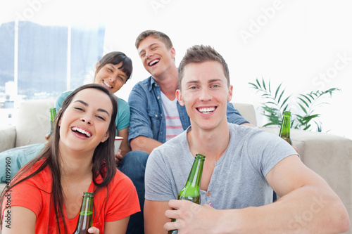 Four people in a living room enjoying beer and having fun togeth