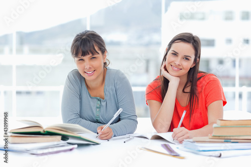 Two smiling students studying together while looking at the came