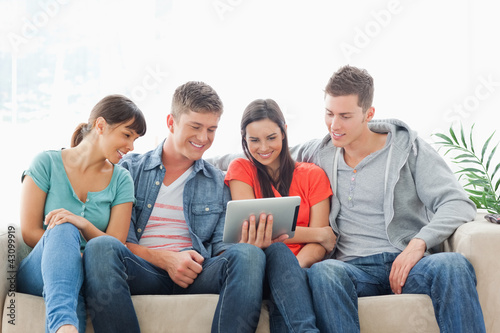 A group of friends sit on the couch while watching a tablet pc